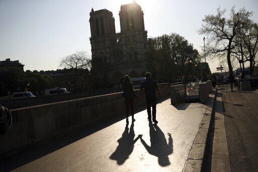 (AP Photo/Francisco Seco). Two people walk by a the Notre Dame Cathedral in Paris, Saturday, April 20, 2019. Yellow vest protests are scheduled to take place in Paris and other regions of France over the weekend, with a heightened security presence ant...