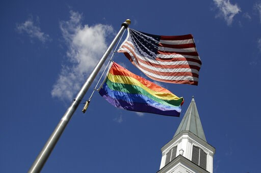 (AP Photo/Charlie Riedel). A gay pride rainbow flag flies along with the U.S. flag in front of the Asbury United Methodist Church in Prairie Village, Kan., on Friday, April 19, 2019. There's at least one area of agreement among conservative, centrist a...