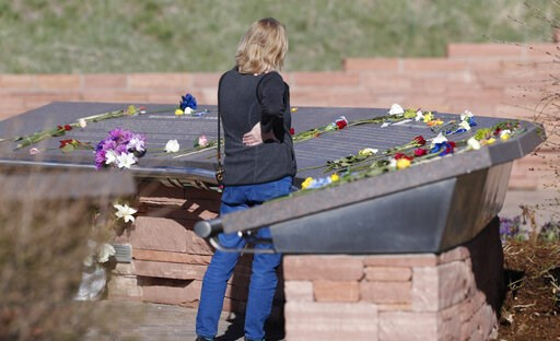(AP Photo/David Zalubowski). A woman looks over the stories of the slain before a vigil at the memorial for the victims of the massacre at Columbine High School nearly 20 years ago Friday, April 19, 2019, in Littleton, Colo.