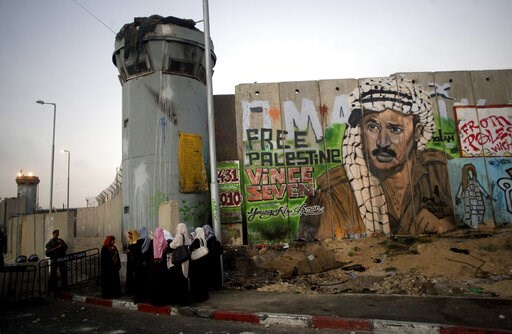 (AP Photo/Sebastian Scheiner, File). File - In this Friday, Aug. 13, 2010 file photo, Palestinian women wait near a section of Israel's separation barrier covered in graffiti, one depicting the late Palestinian leader Yasser Arafat, at the Qalandiya ch...