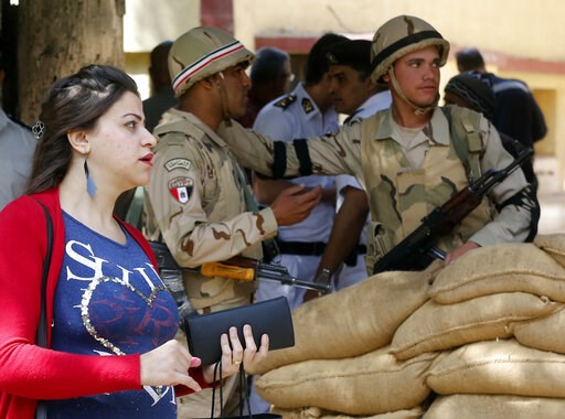 (AP Photo/Amr Nabil). A voter leaves a polling station guarded by soldiers after she casting her ballot on constitutional amendments during the first day of three-day voting in Cairo, Egypt, Saturday, April 20, 2019. Egyptians are voting on constitutio...