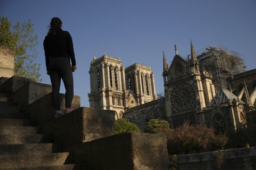(AP Photo/Francisco Seco). A woman stands on steps near the Notre Dame Cathedral in Paris, Saturday, April 20, 2019. Rebuilding Notre Dame, the 800-year-old Paris cathedral devastated by fire this week, will cost billions of dollars as architects, hist...