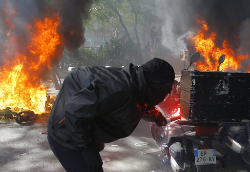 (AP Photo/Michel Euler). A protestor lights a motorbike on fire during a yellow vest demonstration in Paris, Saturday, April 20, 2019. French yellow vest protesters are marching anew to remind the government that rebuilding the fire-ravaged Notre Dame ...