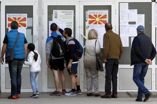 (AP Photo/Boris Grdanoski). People check lists before voting in the presidential election outside a polling station in Skopje, North Macedonia, Sunday, April 21, 2019. Polls were opened early on Sunday in North Macedonia for presidential elections seen...