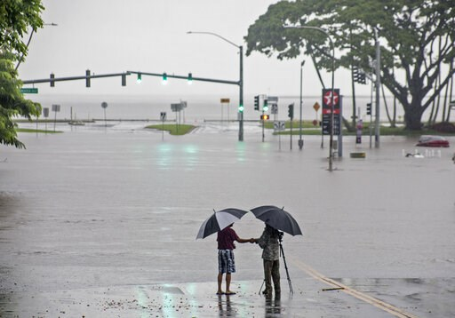 (Hollyn Johnson/Hawaii Tribune-Herald via AP, File). In this Aug. 23, 2018 file photo, people stand near flood waters from Hurricane Lane in Hilo, Hawaii. Some of Hawaii's most iconic beaches could soon be underwater  as rising sea levels caused by glo...