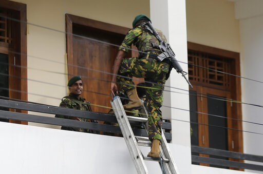 (AP Photo/Eranga Jayawardena). A Sri Lankan police commando enters a house suspected to be a hideout of militants following a shoot out in Colombo, Sri Lanka, Sunday, April 21, 2019.  More than hundred were killed and hundreds more hospitalized with in...