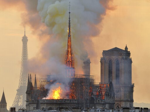 (AP Photo/Thierry Mallet, FILE). FILE - In this file photo dated Monday, April 15, 2019, with the Eiffel Tower behind, left, flames and smoke rise from the blaze at Notre Dame Cathedral in Paris that destroyed its spire and its roof but spared its twin...