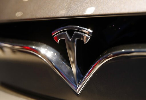(AP Photo/Christophe Ena, File). FILE- This Oct. 3, 2018, file photo shows a Tesla emblem at the Auto show in Paris. Tesla CEO Elon Musk appears poised to transform the company's electric cars into driverless vehicles in a risky bid to realize a bold v...