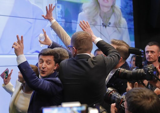 (AP Photo/Vadim Ghirda). In this Sunday, April 21, 2019, photo, Ukrainian comedian and presidential candidate Volodymyr Zelenskiy, left, makes the victory sign after seeing the exit polls for the second round of presidential elections in Kiev, Ukraine....