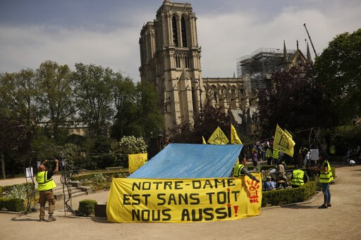 "(AP Photo/Francisco Seco). People fix a banner that reads in French: ""Notre-Dame is roofless, we too!"" during a protest in front of the Notre Dame cathedral in Paris, Monday, April 22, 2019."