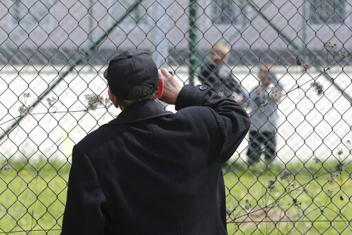 (AP Photo/Visar Kryeziu). Hajdar Selimovic calls to his nephew Ismail behind a fence at a detention center where authorities have brought back from Syria 110 Kosovar citizens, mostly women and children in the village of Vranidol on Sunday, April 20, 20...