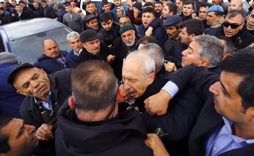 (DHA via AP). A man punches Kemal Kilicdaroglu, the leader of Turkey's main opposition Republican People's Party, during the funeral of a soldier who was slain during clashes with Kurdish rebels at Iraq border, outside Ankara, Turkey, Sunday, April 21,...