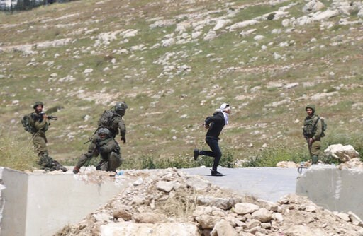 (AP Photo/Mohammad Hmeid). In this Thursday, Apri 18, 2019 photo, handcuffed and blindfolded Osama Hajahjeh, 16, runs away from Israeli soldiers near the village of Tekoa, West Bank. Hajahjeh said was shot in his legs last week by Israeli soldiers whil...