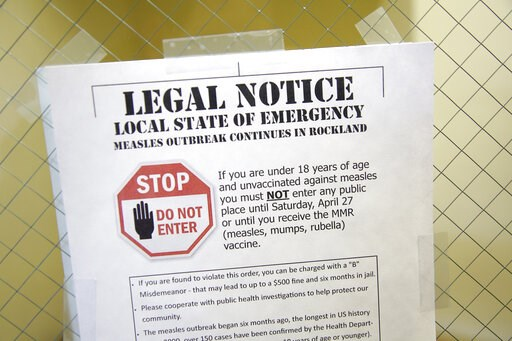 (AP Photo/Seth Wenig, File). FILE - This March 27, 2019 file photo shows a sign explaining the local state of emergency because of a measles outbreak at the Rockland County Health Department in Pomona, N.Y. Outbreaks in New York state continue to drive...