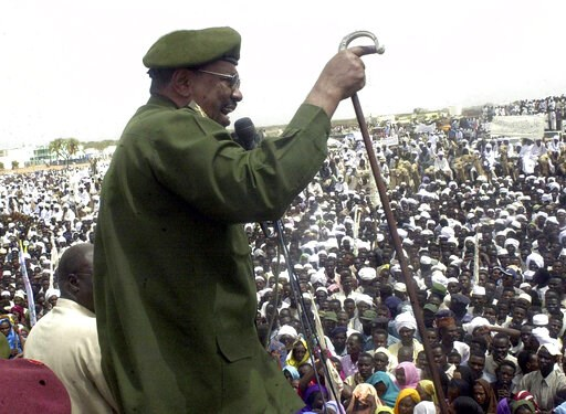 (AP Photo/Abd Raouf, File). FILE - In this May 19, 2004 file photo, then Sudanese President Omar al-Bashir speaks to thousands of Sudanese in Nyala, capital of the country's southern Darfur state. Al-Bashir, driven from power in April 2019, and now lan...