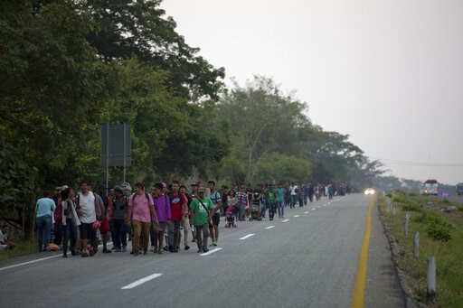 (AP Photo/Moises Castillo). Central American migrants traveling in a caravan to the U.S. border walk on a road in Pijijiapan, Mexico, Monday, April 22, 2019. The outpouring of aid that once greeted Central American migrants as they trekked in caravans ...