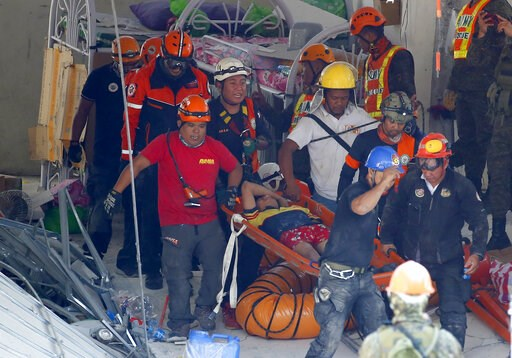 (AP Photo/Bullit Marquez). Rescuers carry an earthquake survivor after being pulled out from the rubble of a commercial building following Monday's 6.1 magnitude earthquake in Porac township, Pampanga province, north of Manila, Philippines, Tuesday, Ap...