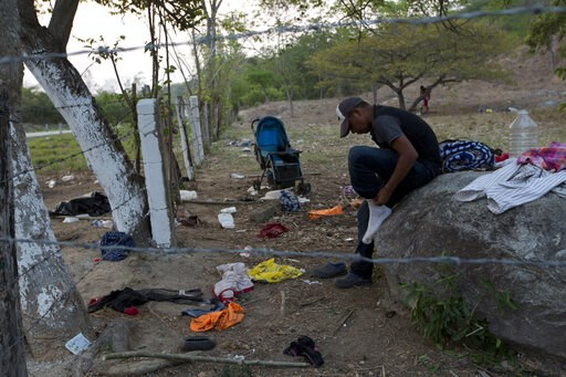 (AP Photo/Moises Castillo). A migrant puts on the socks he'd left behind when his group evaded Mexican immigration agents by running away from the highway and into the brush in Pijijiapan, Chiapas state, Mexico, Monday, April 22, 2019. Mexican police a...