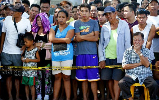 (AP Photo/Bullit Marquez). Residents watch as rescuers continue to search for survivors following Monday's 6.1 magnitude earthquake that caused the collapse of a commercial building in Porac township, Pampanga province, north of Manila, Philippines, Tu...
