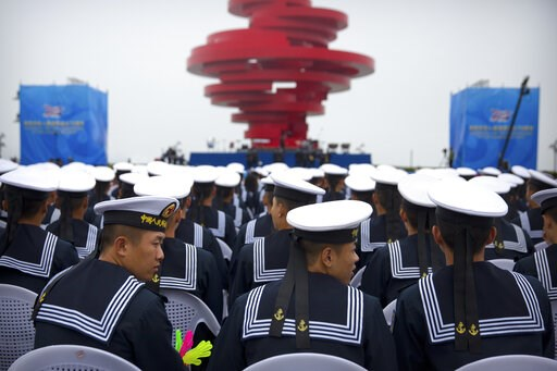 (AP Photo/Mark Schiefelbein). Chinese sailors sit during a concert featuring Chinese and foreign military bands in Qingdao, Monday, April 22, 2019. Ships from Chinese and foreign navies have gathered in Qingdao for events this week, including a naval p...