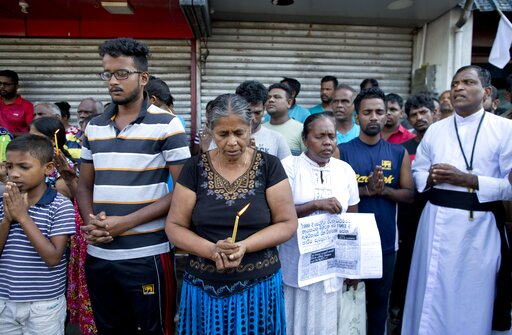(AP Photo/Gemunu Amarasinghe). People pray during a nationwide three-minutes silence as a tribute to Easter Sunday attack victims in Colombo, Sri Lanka, Tuesday, April 23, 2019. Easter Sunday bombings of churches, luxury hotels and other sites was Sri ...