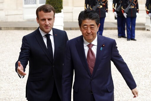 (AP Photo/Thibault Camus). French President Emmanuel Macron, left welcomes Japan's Prime Minister Shinzo Abe wave before their talks at the Elysee Palace, Tuesday, April 23, 2019 in Paris.