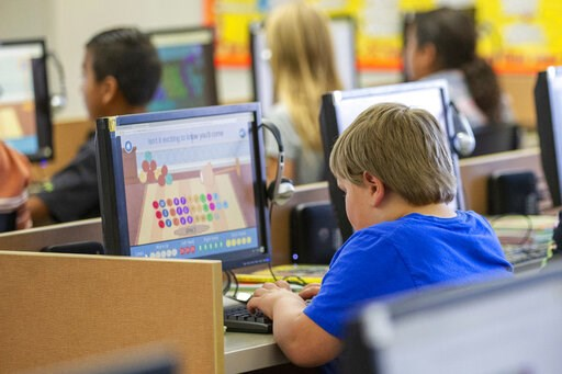 (Scott G Winterton/The Deseret News via AP). FILE - In this Oct. 29, 2018 file photo, students work on computers at an elementary school in Beaver, Utah. According to a study published on Tuesday, April 23, 2019, Americans are becoming increasingly sed...