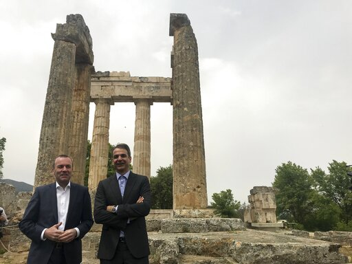 (AP Photo/Derek Gatopoulos). European People's Party candidate Manfred Weber, left, and the leader of Greece's conservative New Democracy party Kyriakos Mitsotakis visit an ancient temple at Nemea about 117 kilometers (73 miles) west of Athens on Tuesd...