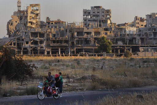 (AP Photo/Sergei Grits). FILE - In this Aug. 15, 2018 file photo, people ride their motorcycle by damaged buildings in the old town of Homs, Syria.   Syrian government forces came under separate attacks from Islamic State militants and al-Qaida-linked ...