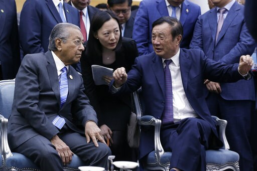 (AP Photo/Andy Wong). Huawei founder and CEO Ren Zhengfei, right, explains the 5G network system to Malaysian Prime Minister Mahathir Mohamad, left, as Mahathir visits to Huawei Executive Briefing Center in Beijing, Thursday, April 25, 2019. Mahathir i...