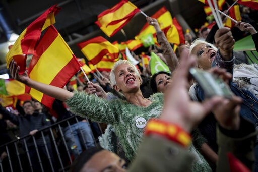 (AP Photo/Bernat Armangue). In this Saturday, April 6, 2019 photo, supporters of Spain's far-right Vox Party wave Spanish and VOX flags during a party event in Leganes, on the outskirts of Madrid, Spain. A substantial pool of undecided voters and a rig...
