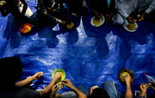 (AP Photo/Gemunu Amarasinghe). Ahmadi Muslim refugees eat a meal at a community center that they took refuge in Pasyala, north east of Colombo, Sri Lanka, Thursday, April 25, 2019. Hundreds of Ahmadi Muslims from Pakistan who sought refuge in Sri Lanka...