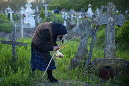 (AP Photo/Andreea Alexandru). An elderly woman walks to a relative's graves at dawn in Copaciu, southern Romania, Thursday, April 25, 2019. On Maundy Thursday during the holy week of Easter, Orthodox Christians in small southern Romanian villages go to...