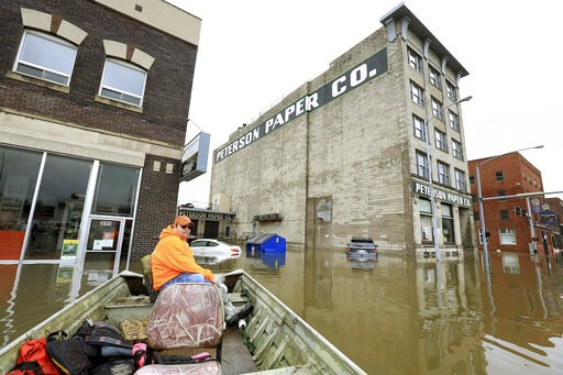 (Kevin E. Schmidt/Quad City Times via AP). Ryan Lincoln maneuvers his boat through flood water at the intersection of Pershing Ave and E 2nd St. Thursday, May 2, 2019. Lincoln's employer Hahn Ready Mix allowed him to take time off from work to voluntee...