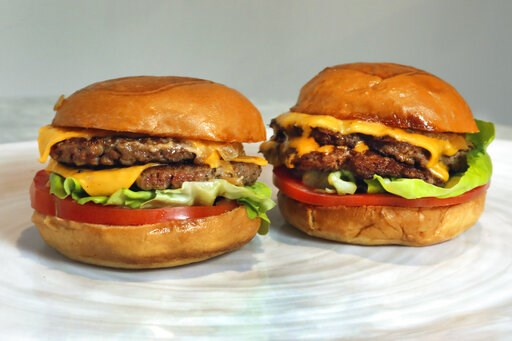 (AP Photo/Richard Drew). An Original Impossible Burger, left, and a Cali Burger, from Umami Burger, are shown in this photo in New York, Friday, May 3, 2019. A new era of meat alternatives is here, with Beyond Meat becoming the first vegan meat company...