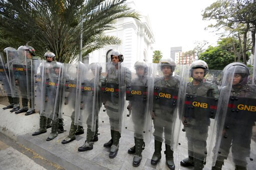 (AP Photo/Fernando Llano). Venezuelan Bolivarian National guards officers form a cordon around the National Assembly building as the opposition-controlled congress met to discuss a move that could provide political cover for greater international invol...