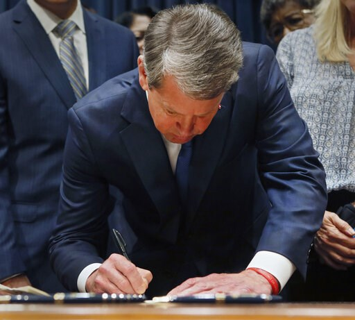 (Bob Andres/Atlanta Journal-Constitution via AP). Georgia's Republican Gov. Brian Kemp signs legislation, Tuesday, May 7, 2019, in Atlanta, banning abortions once a fetal heartbeat can be detected, which can be as early as six weeks before many women k...