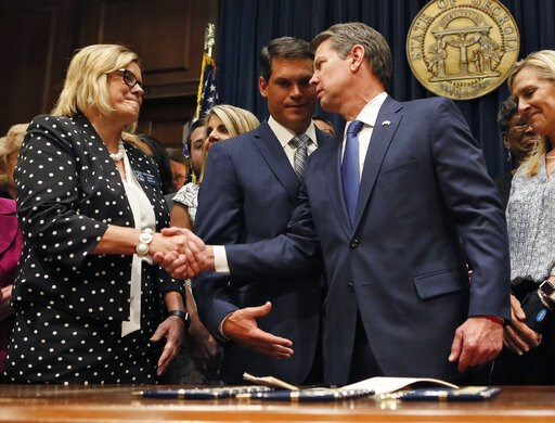 (Bob Andres/Atlanta Journal-Constitution via AP). Georgia's Republican Gov. Brian Kemp, right, shakes hands with state Sen. Renee Unterman, R-Buford, after signing legislation, Tuesday, May 7, 2019, in Atlanta, banning abortions once a fetal heartbeat ...