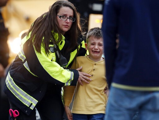(AP Photo/David Zalubowski). RETRANSMIT WITH ALTERNATE CROP Officials guide students off a bus and into a recreation center where they were reunited with their parents after a shooting at a suburban Denver middle school Tuesday, May 7, 2019, in Highlan...