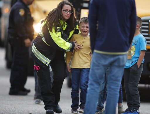 (AP Photo/David Zalubowski). Officials guide students off a bus and into a recreation center where they were reunited with their parents after a shooting at a suburban Denver middle school Tuesday, May 7, 2019, in Highlands Ranch, Colo.