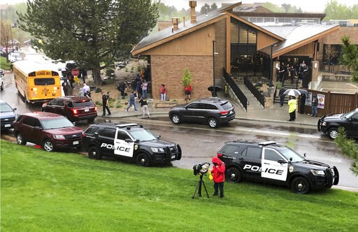 (AP Photo/David Zalubowski). CORRECTS TO A RECREATION CENTER Police and others are seen outside a recreation center where students are reunited with their parents, in the Denver suburb of Highlands Ranch, Colo., after a shooting at STEM School Highland...