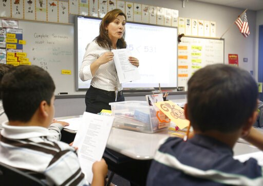 (AP Photo/Rich Pedroncelli, File). FILE - In this June 12, 2013 file photo second-grade teacher Vickie Boudouris goes over a an English work sheet with her students at the Cordova Villa Elementary School, in Rancho Cordova, Calif. The California State ...