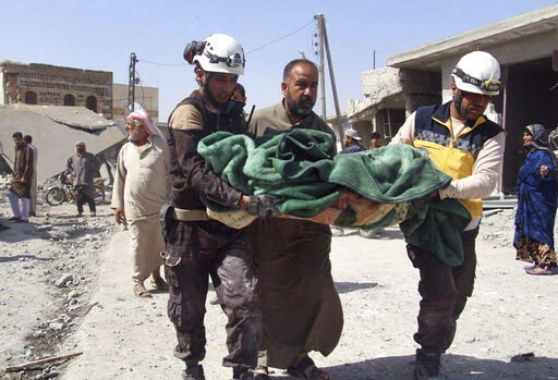 (Syrian Civil Defense White Helmets via AP). This photo provided by the Syrian Civil Defense group known as the White Helmets, shows members of the Syrian Civil Defense workers carrying a victim after a deadly airstrike hit a market killing several peo...