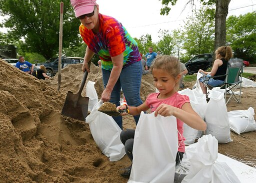 (David Carson/St. Louis Post-Dispatch via AP). Barbara Moore, left, and her granddaughter Amaya Ward, 7, fill sandbags with other volunteers at the Cherokee Lakes Campground in O'Fallon, Mo., Tuesday, May 7, 2019. The levee at the campground began leak...