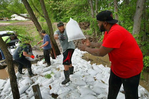 (David Carson/St. Louis Post-Dispatch via AP). Marcus Gilbert, center,  tosses a sandbag to Herman Drones as they and other volunteers work to plug the leaks in a levee at Cherokee Lakes Campground in O'Fallon, Mo., Tuesday, May 7, 2019. The levee bega...