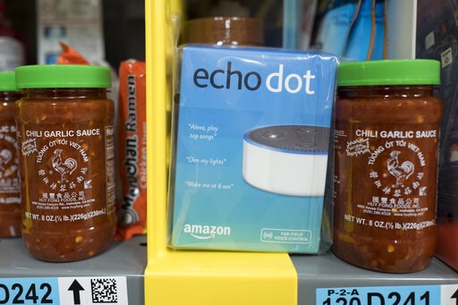 (AP Photo/Mark Lennihan, File). FILE - This Dec. 20, 2017, file photo shows the Amazon Echo Dot stocked on a shelf alongside jars of Garlic Chili Sauce at the Amazon Prime warehouse in New York. Consumer advocates say the kids' version of Amazon's Alex...