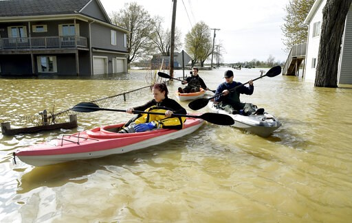 (Tom Hawley/The Monroe News via AP). In this Wednesday, May 8, 2019 photo, Estral Beach Firefighters Courtney Millar, Eric Bruley, and Chase Baldwin kayak down Lakeshore Dr. in the south end of Estral Beach in Berlin Township, Mich., to see if anyone n...