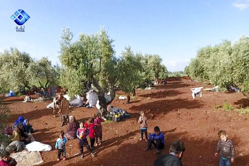 (Thiqa News Agency via AP). This frame grab from video provided by the activist-operated Thiqa News Agency, shows residents displaced from the latest violence that hit the last rebel stronghold, taking refuge in olives orchids near the town of al-Atmeh...