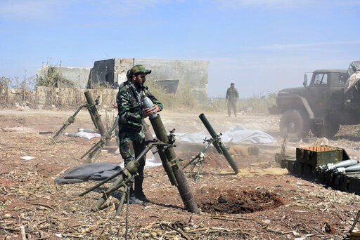 (SANA via AP). In this photo released by the Syrian official news agency SANA, Syrian army soldiers prepare to launch a mortar towards insurgents in the village of Kfar Nabuda, in the countryside of Hama province on Saturday, May 11, 2019. The Britain-...