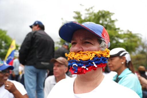 (AP Photo/Martin Mejia). An opponent of the Nicolas Maduro government, his mouth covered with strands representing the national colors of Venezuela, waits for the arrival of opposition leader Juan Guaidó to lead a rally in Caracas, Venezuela, Saturday,...